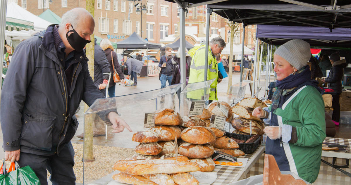 A gentleman buying bread from the lady in green at the Farmers Market Epsom