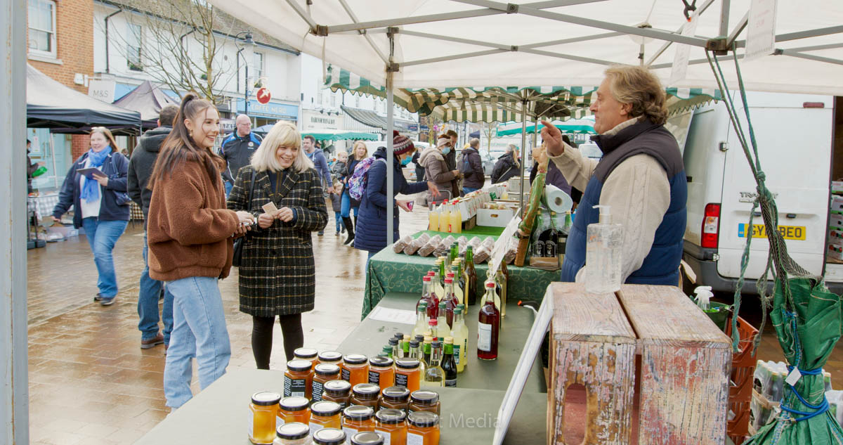 A stall holder having a friendly conversation with is customers at the Farmers Market Epsom