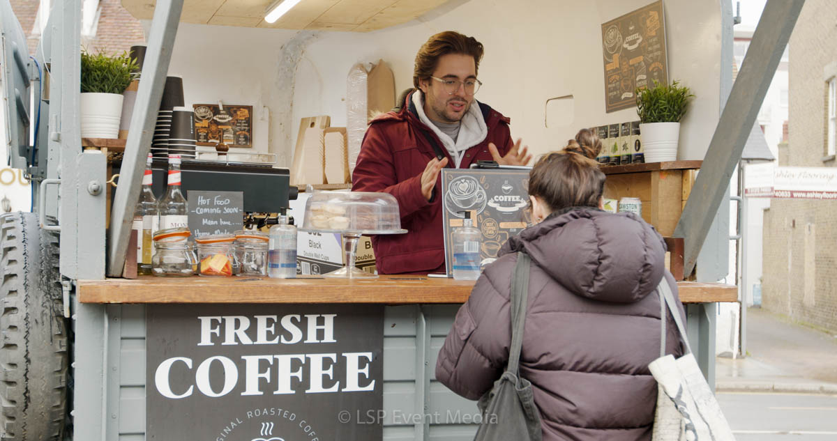 An stall holder selling fresh coffee to a lady at the Farmers Market Epsom